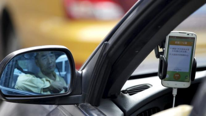 A taxi driver is reflected in a side mirror as he uses the Didi Chuxing car-hailing application in Beijing, China, September 22, 2015. REUTERS/Jason Lee